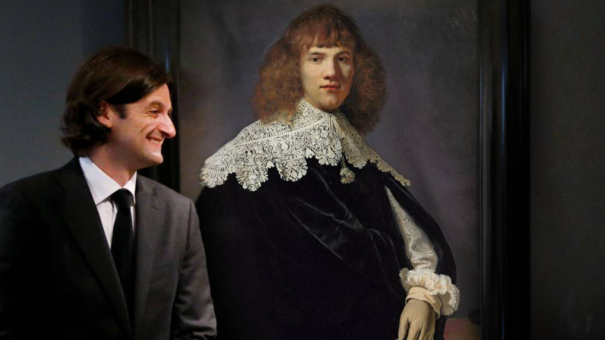 a young man in a suit next to a Rembrandt