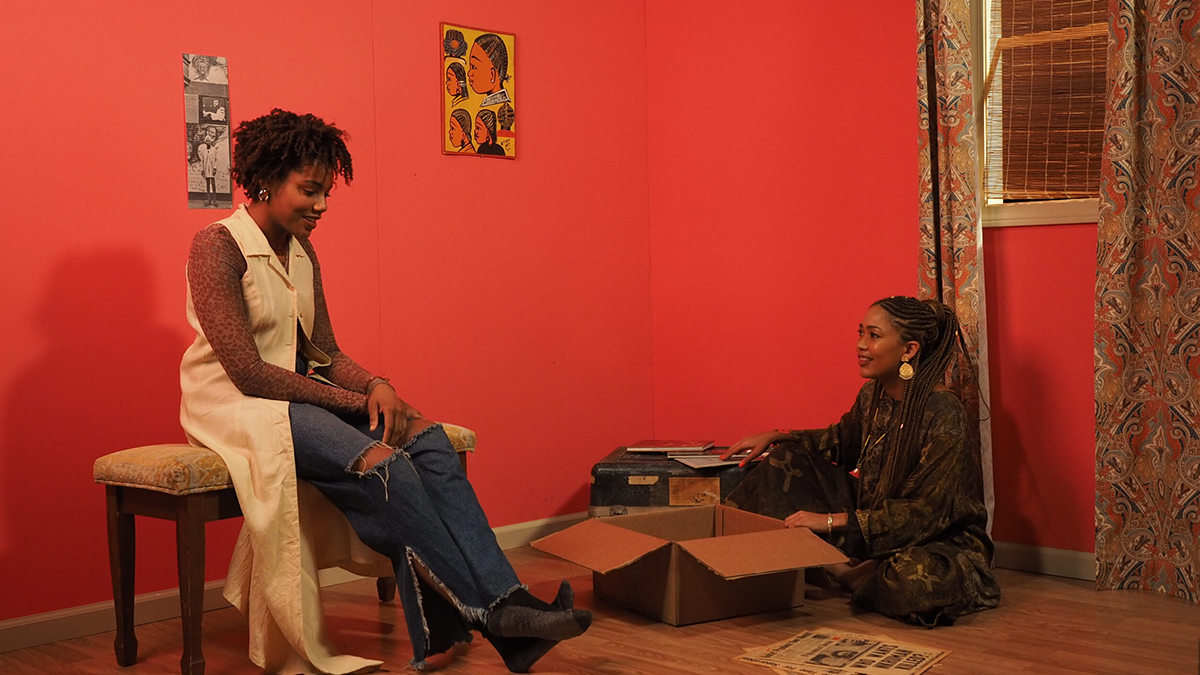Two people conversing in a red room