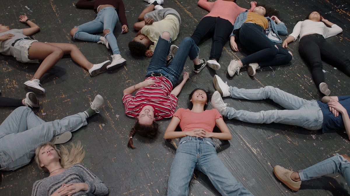 many young people lying on their backs, smiling