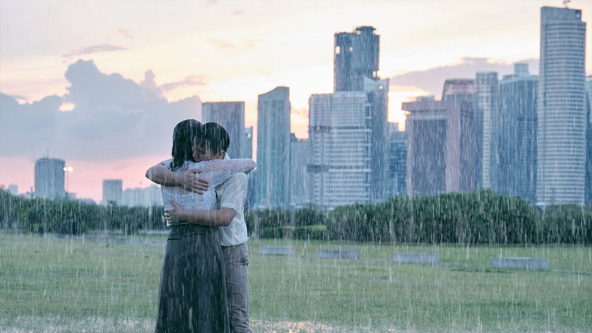 people embracing in the rain with a skyline in the background