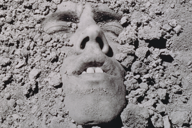 Person's face pertruding out of gravel