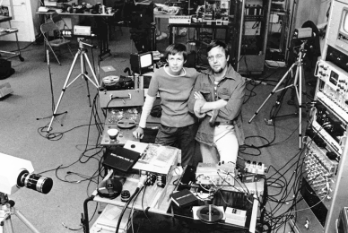 two people looking at the camera surrounded by tech gear